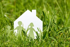 A paper-cutout of a family in front of a paper cutout of a house, in a rural field of grass.