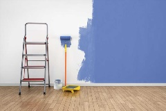 Step ladder and roller brush leaning against a half-painted blue wall.